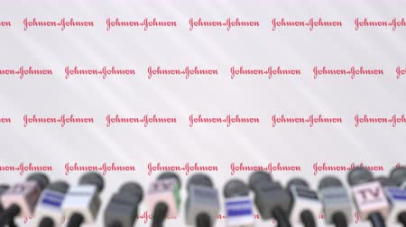 declaring : Press conference of JOHNSON AND JOHNSON, press wall with logo and microphones, conceptual editorial animation