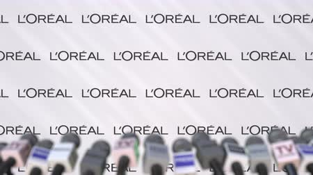 declaring : Press conference of LOREAL, press wall with logo and microphones, conceptual editorial animation