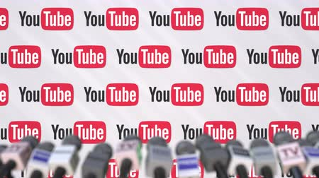 declaring : Press conference of YOUTUBE, press wall with logo and microphones, conceptual editorial animation