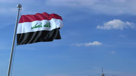海外で : Commercial airplane landing behind waving Iraqi flag. Travel to Iraq conceptual animation