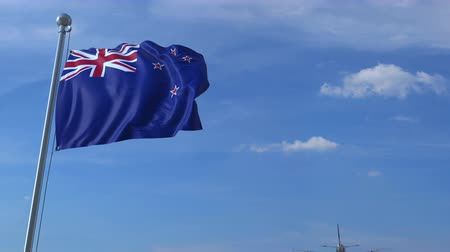 nowa zelandia : Commercial airplane landing behind waving flag. Travel to New Zealand conceptual animation