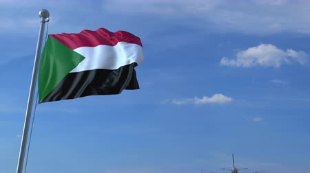sudanian : Commercial airplane landing behind waving Sudanian flag. Travel to Sudan conceptual animation