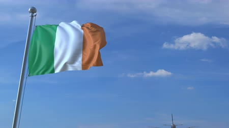 drapeau irlandais : Commercial airplane landing behind waving Irish flag. Travel to the Republic of Ireland conceptual animation