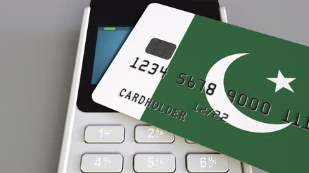 дебет : Payment terminal with credit card featuring flag of Pakistan. Pakistani national banking system conceptual 3D animation Стоковые видеозаписи