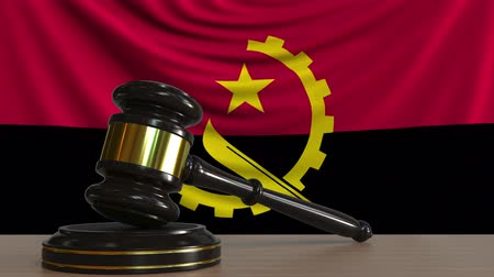 árverezői kalapács : Judges gavel and block against the flag of Angola. Angolan court conceptual animation Stock mozgókép