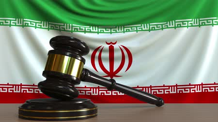 судья : Judges gavel and block against the flag of Iran. Iranian court conceptual animation Стоковые видеозаписи