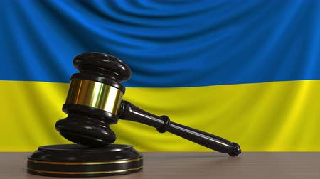 árverezői kalapács : Judges gavel and block against the flag of Ukraine. Ukrainian court conceptual animation