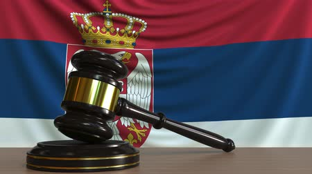 licit : Judges gavel and block against the flag of Serbia. Serbian court conceptual animation Stock Footage