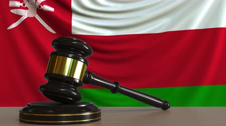 adli : Judges gavel and block against the flag of Oman. Omani court conceptual animation Stok Video