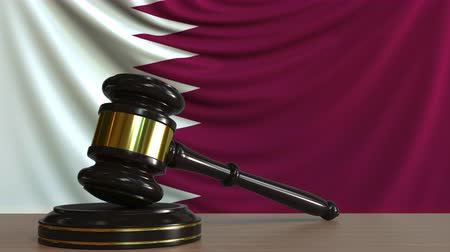 судья : Judges gavel and block against the flag of Qatar. Qatari court conceptual animation Стоковые видеозаписи
