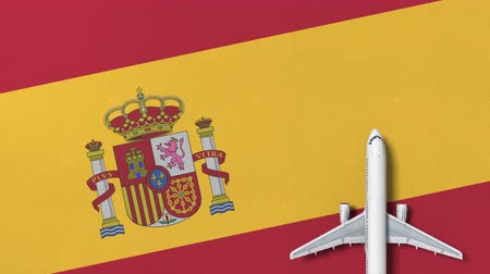 flat lay : Commercial airplane on the flag of Spain. Travel related conceptual 3D animation Stock Footage