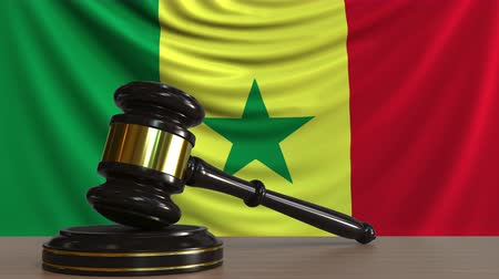 licit : Judges gavel and block against the flag of Senegal. Senegalese court conceptual animation