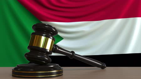 adli : Judges gavel and block against the flag of Sudan. Sudanese court conceptual animation