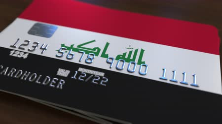 bankomat : Plastic bank card featuring flag of Iraq. Iraqi national banking system related animation