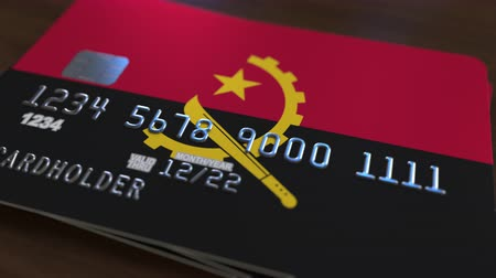 bankomat : Plastic bank card featuring flag of Angola. Angolan national banking system related animation Wideo