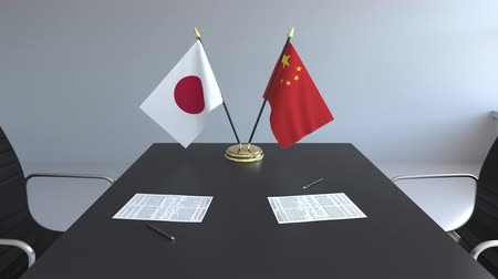 assinatura : Flags of Japan and China and papers on the table. Negotiations and signing an international agreement. Conceptual 3D animation