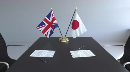assinatura : Flags of Great Britain and Japan and papers on the table. Negotiations and signing an international agreement. Conceptual 3D animation