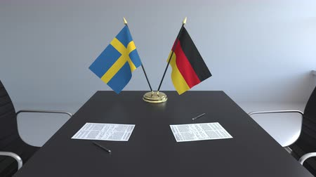 assinatura : Flags of Sweden and Germany and papers on the table. Negotiations and signing an international agreement. Conceptual 3D animation