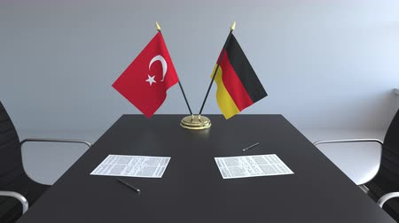 assinatura : Flags of Turkey and Germany and papers on the table. Negotiations and signing an international agreement. Conceptual 3D animation