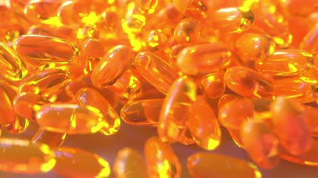 omega : Pouring fish oil or orange drug capsules on the table. Realistic 3D animation Stock Footage