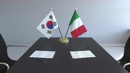 diplomatie : Flags of South Korea and Italy and papers on the table. Negotiations and signing an international agreement. Conceptual 3D animation