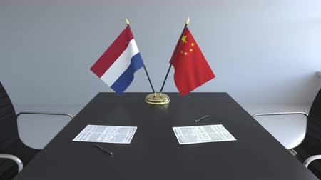 assinatura : Flags of Netherlands and China and papers on the table. Negotiations and signing an international agreement. Conceptual 3D animation