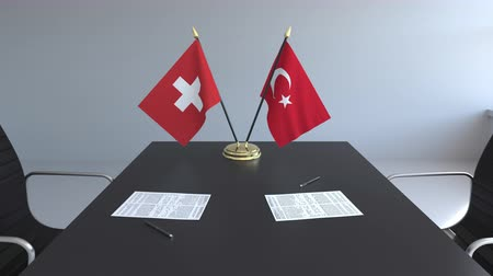 assinatura : Flags of Switzerland and Turkey and papers on the table. Negotiations and signing an international agreement. Conceptual 3D animation