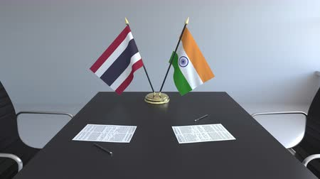 diplomatie : Flags of Thailand and India and papers on the table. Negotiations and signing an international agreement. Conceptual 3D animation Vidéos Libres De Droits