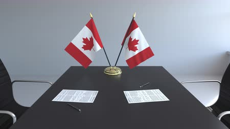 ondertekening : Flags of Canada and papers on the table. Negotiations and signing an agreement. Conceptual 3D animation