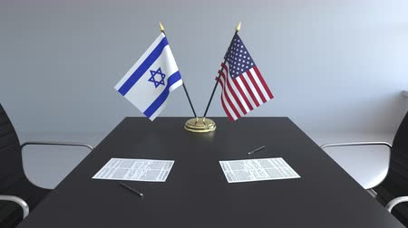 izrael : Flags of Israel and the United States and papers on the table. Negotiations and signing an international agreement. Conceptual 3D animation Stock mozgókép