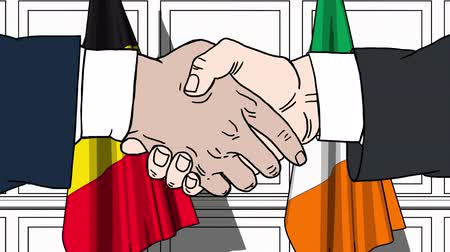 bélgica : Businessmen or politicians shake hands against flags of Belgium and Ireland. Official meeting or cooperation related cartoon animation Stock Footage