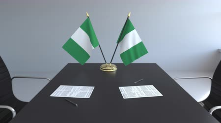 nigeria flag : Flags of Nigeria and papers on the table. Negotiations and signing an agreement. Conceptual 3D animation Stock Footage