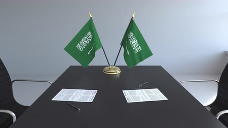ondertekening : Flags of Saudi Arabia and papers on the table. Negotiations and signing an agreement. Conceptual 3D animation Stockvideo