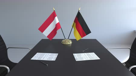 assinatura : Flags of Austria and Germany and papers on the table. Negotiations and signing an international agreement. Conceptual 3D animation