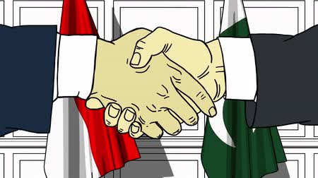 diplomatie : Businessmen or politicians shake hands against flags of Indonesia and Pakistan. Official meeting or cooperation related cartoon animation