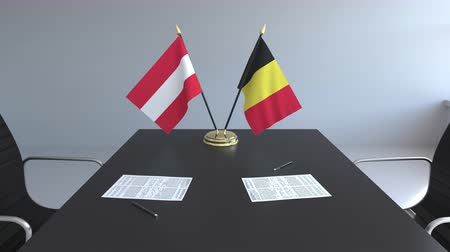 assinatura : Flags of Austria and Belgium and papers on the table. Negotiations and signing an international agreement. Conceptual 3D animation