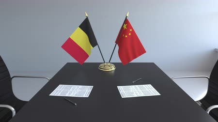 belgio : Flags of Belgium and China and papers on the table. Negotiations and signing an international agreement. Conceptual 3D animation Filmati Stock