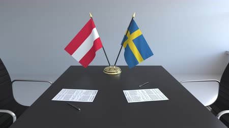 İsveççe : Flags of Austria and Sweden and papers on the table. Negotiations and signing an international agreement. Conceptual 3D animation Stok Video