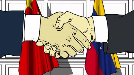 treaty : Businessmen or politicians shake hands against flags of China and Venezuela. Official meeting or cooperation related cartoon animation Stock Footage