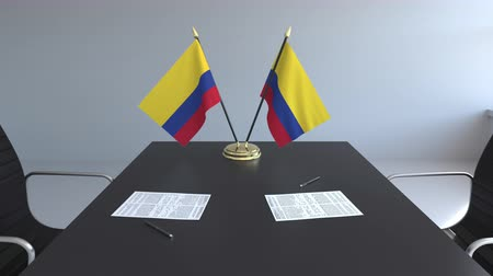 colômbia : Flags of Colombia and papers on the table. Negotiations and signing an agreement. Conceptual 3D animation