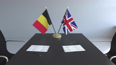bélgica : Flags of Belgium and Great Britain and papers on the table. Negotiations and signing an international agreement. Conceptual 3D animation Stock Footage