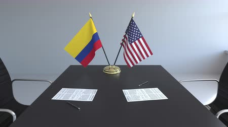 colômbia : Flags of Colombia and the United States of America and papers on the table. Negotiations and signing an international agreement. Conceptual 3D animation Vídeos