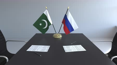 negotiations : Flags of Pakistan and Russia and papers on the table. Negotiations and signing an international agreement. Conceptual 3D animation