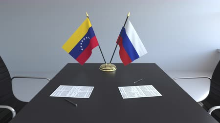diplomatie : Drapeaux du Venezuela et de la Russie et papiers sur la table. Négociations et signature d'un accord international. Animation 3D conceptuelle