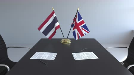 assinatura : Flags of Thailand and the United Kingdom and papers on the table. Negotiations and signing an international agreement. Conceptual 3D animation