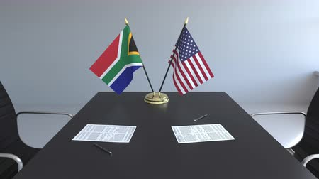 assinatura : Flags of South Africa and the USA and papers on the table. Negotiations and signing an international agreement. Conceptual 3D animation