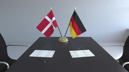 mitgliedschaft : Flags of Denmark and Germany and papers on the table. Negotiations and signing an international agreement. Conceptual 3D animation