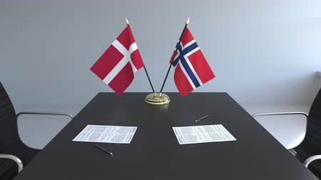 noruega : Flags of Denmark and Norway and papers on the table. Negotiations and signing an international agreement. Conceptual 3D animation