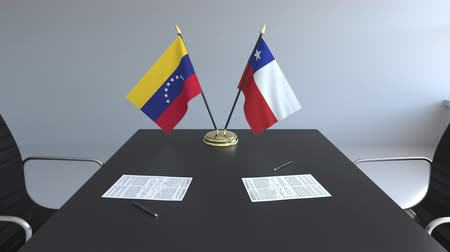 chileno : Flags of Venezuela and Chile and papers on the table. Negotiations and signing an international agreement. Conceptual 3D animation