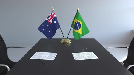 brasileiro : Flags of Australia and Brazil and papers on the table. Negotiations and signing an international agreement. Conceptual 3D animation Stock Footage